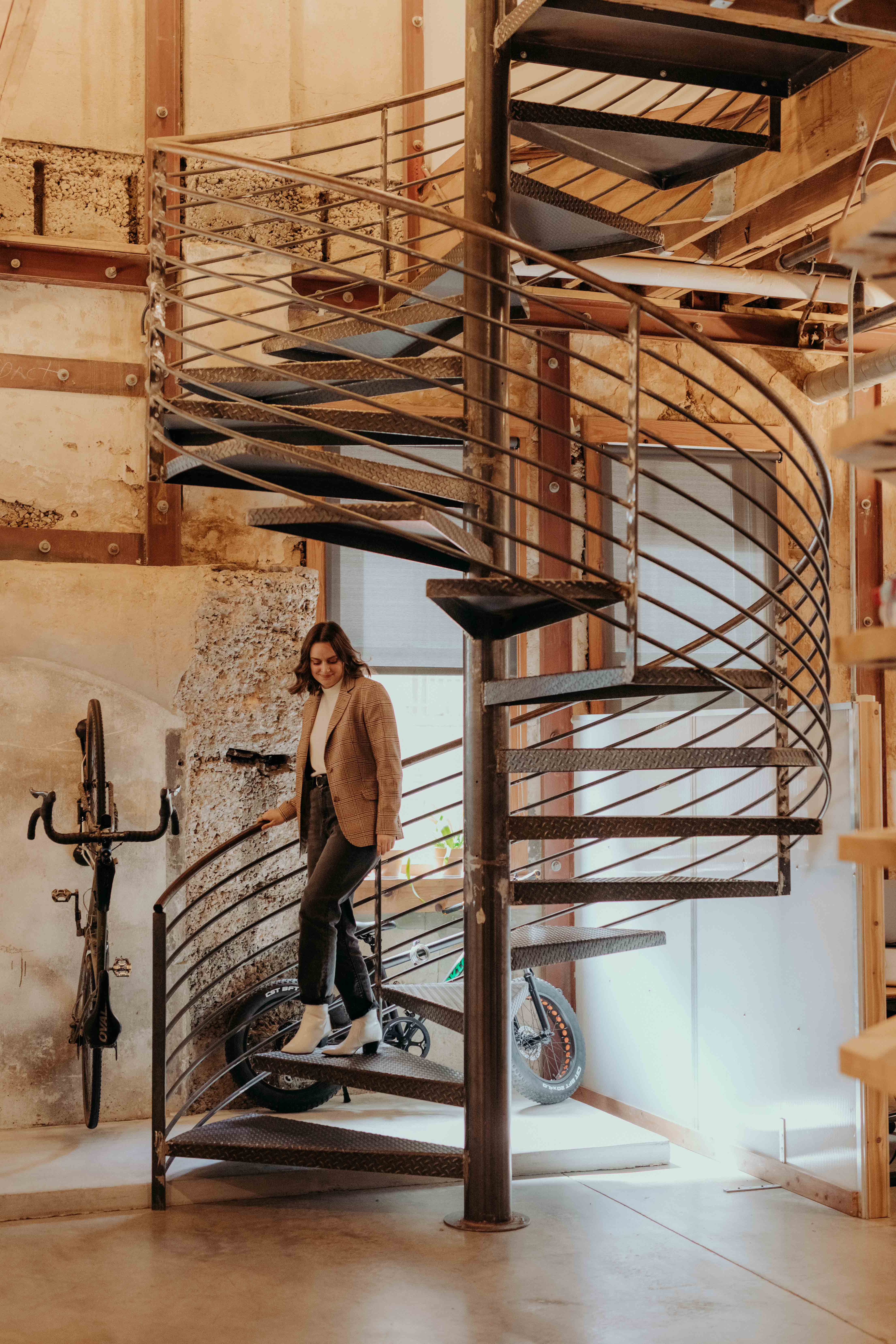 A whiteboard employee ascends the spiral staircase at the office.