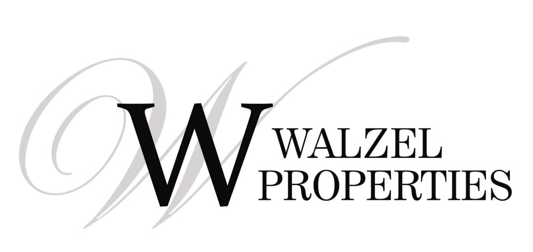 The Walzel Properties company logo featured on a mock-up of a laptop.