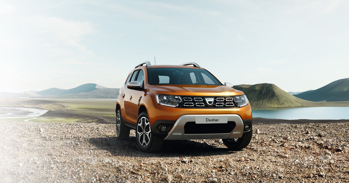 Dacia Duster on gravel with a lake and mountain range backdrop