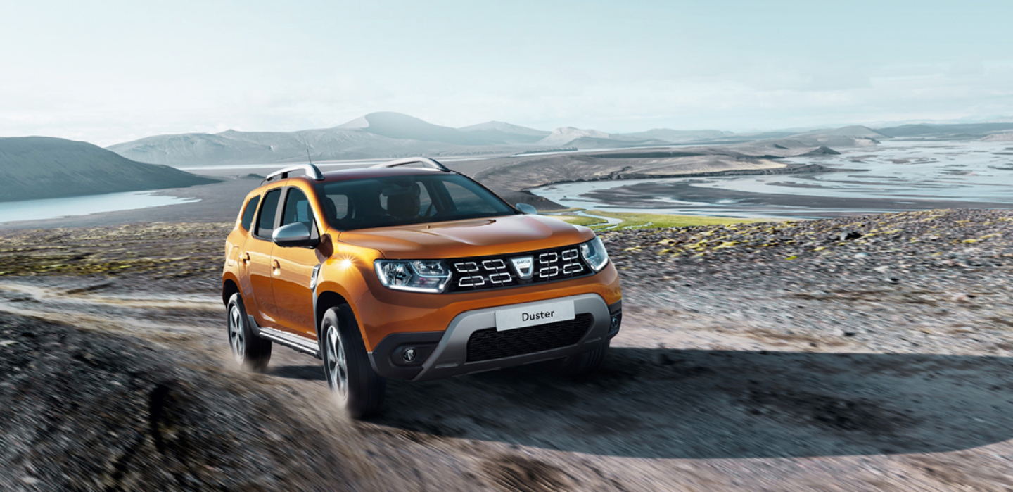 Dacia Duster on gravel road with a dried up lake bed behind