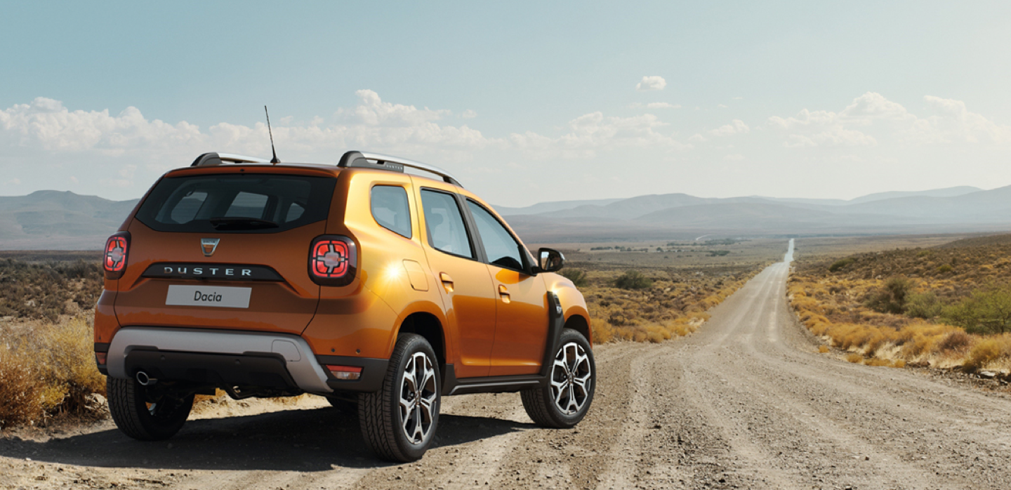 Dacia Duster on gravel road that stretches into the horizon