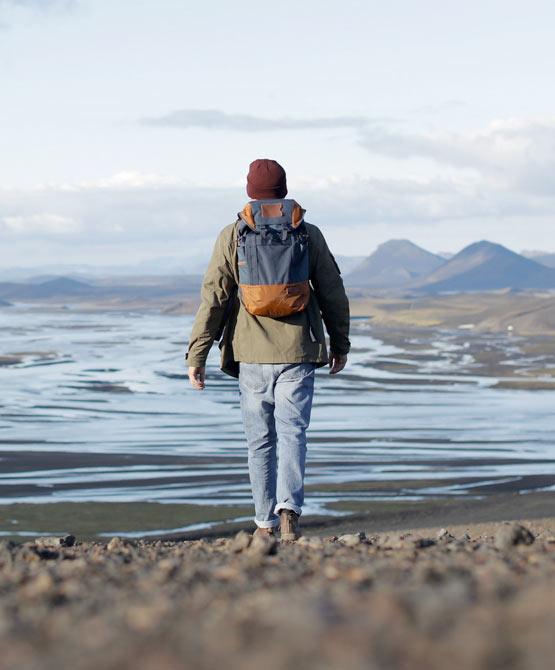 Man walking towards dried up lake