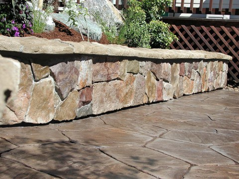 """One of the problems with cultured stone - a cultured stone wall """"floating"""" above a patio."""