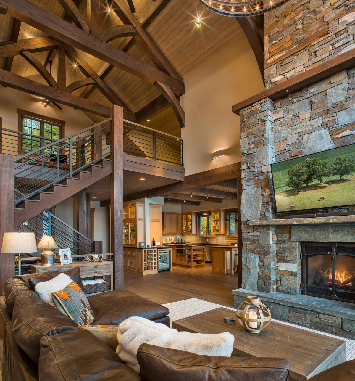 Soaring living room with fireplace and timber trusses
