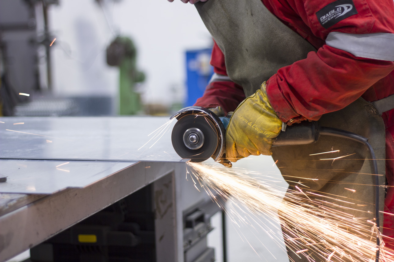 A grinder cutting steel with sparks flying, showing construction.