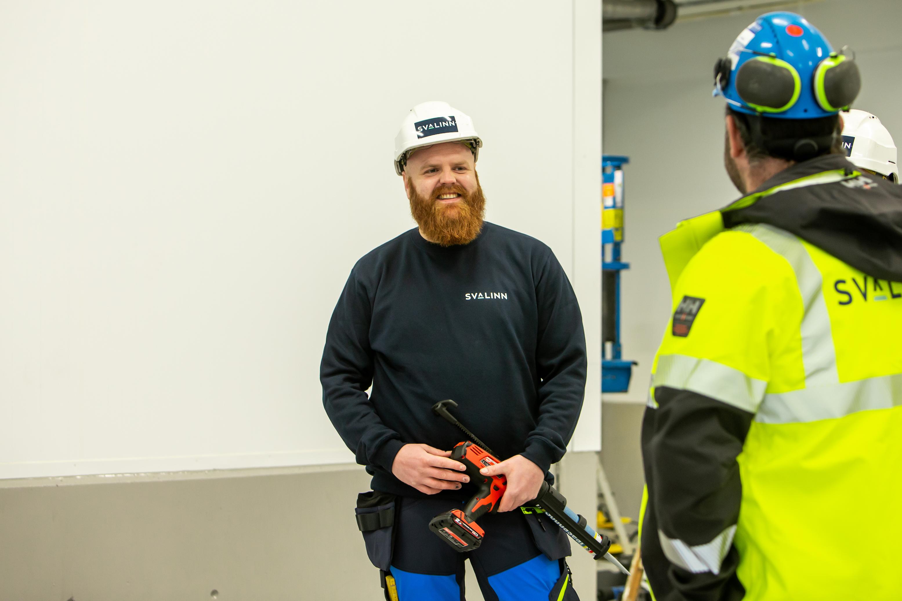 Smilende montør på bygeplass med hard hjelm i montørbekledning.