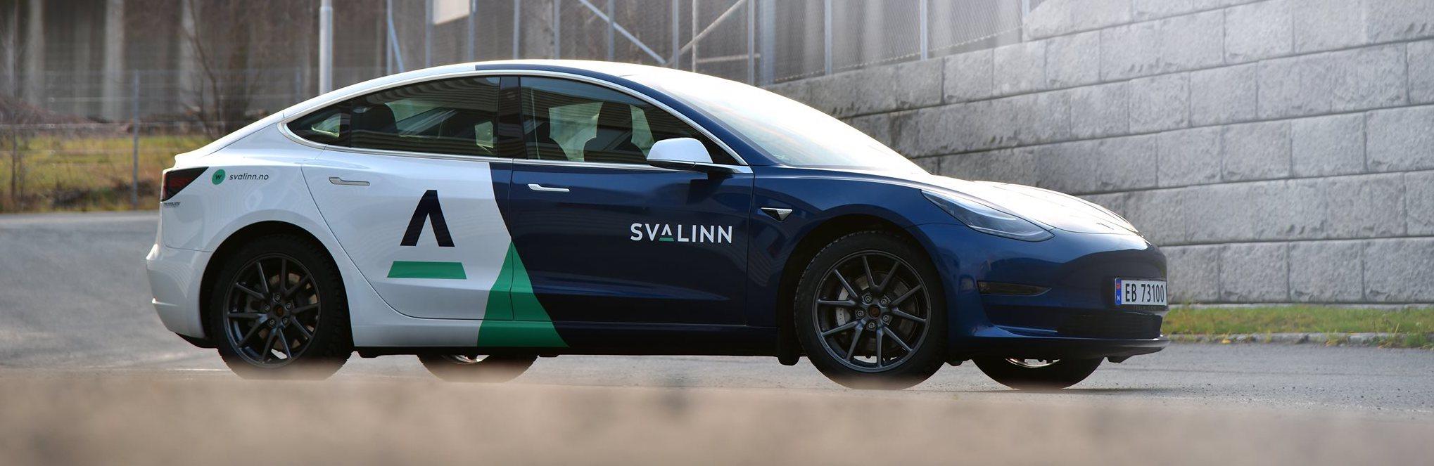 Elektrisk bil Tesla med Svalinn profilering står foran en mur i solskinn