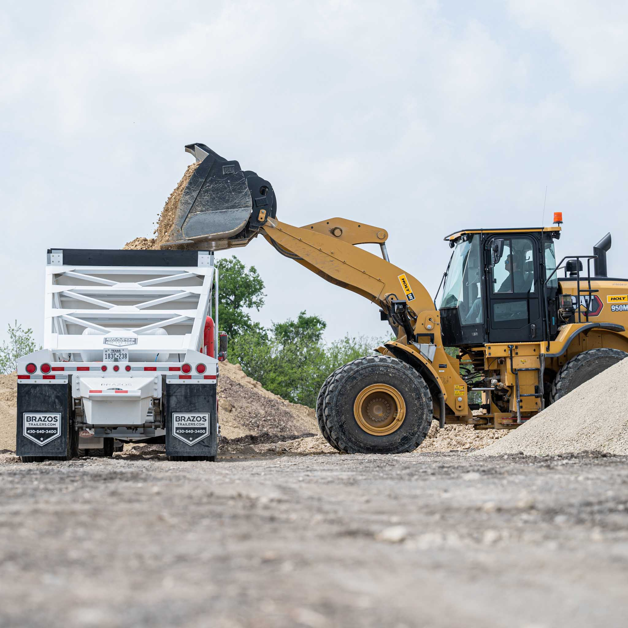 Excavator moving dirt into a haul truck