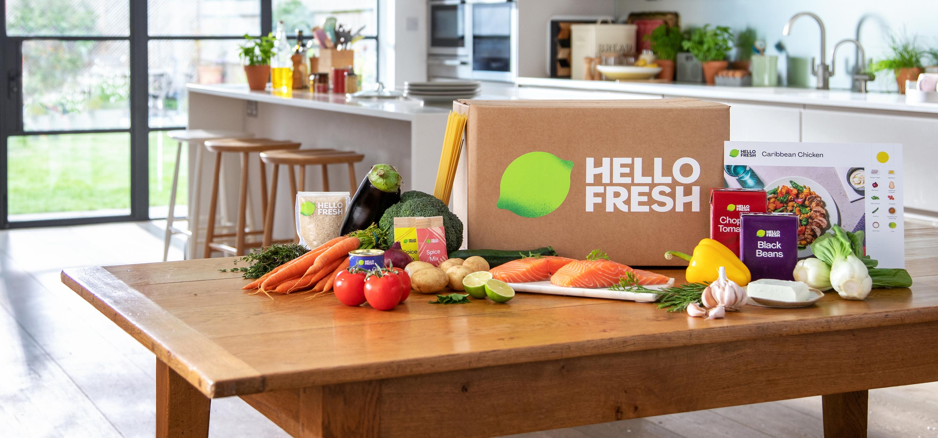 Pappkasse med HelloFresh logo med grønnsaker på et bord på et kjøkken.