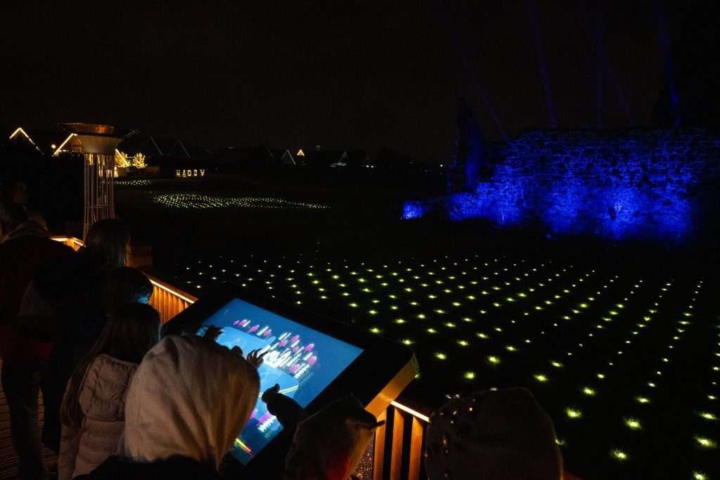 Person using interactive touchscreen at Field of lights