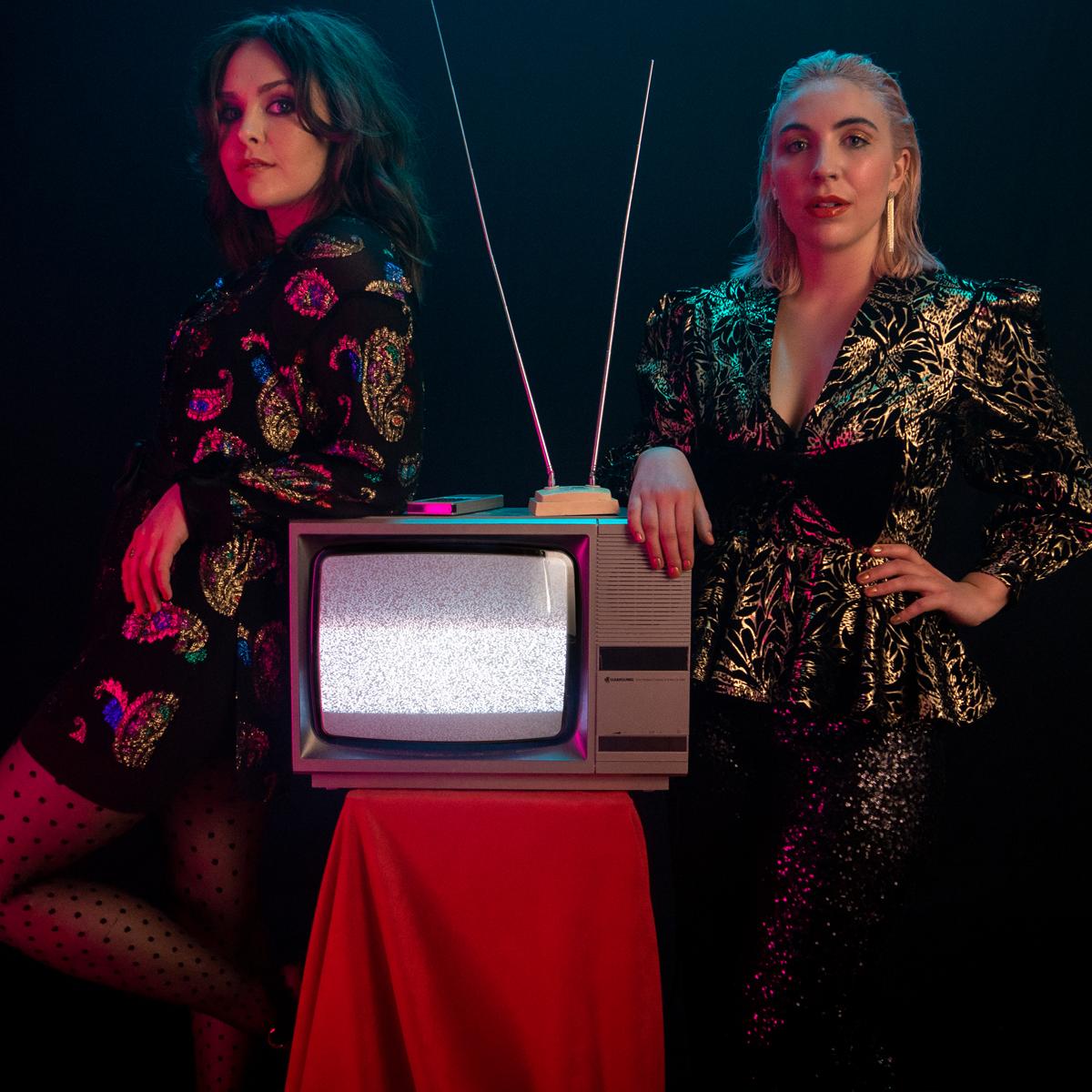 Saint Sister beside a Karaoke TV