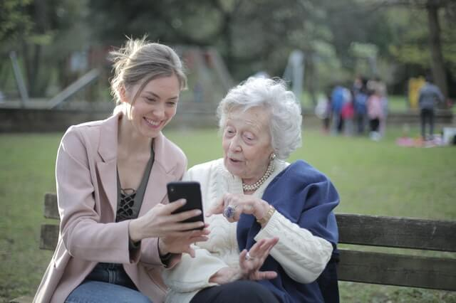Grandma and granddaughter looking at mobile device