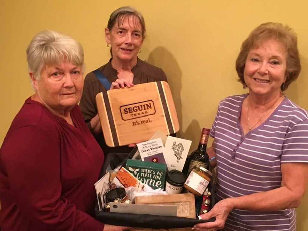 Edith Lange, Janet Wolber and Carol Durben show off one of the three Seguin gift baskets and cutting boards being given away during the Seguin Conservation Society holiday raffle.