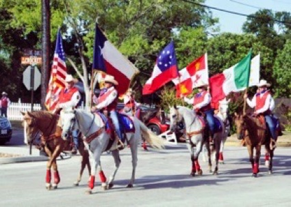Men riding horses and carrying flags at a parade.
