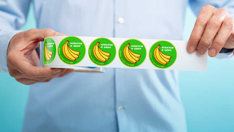 Image of man holding stickers with banana icons on top