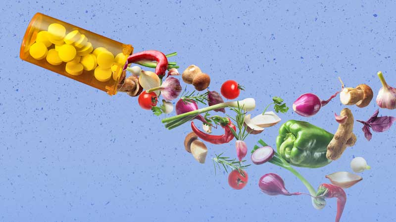 Image of pill bottle with vegetables and fruits coming out of it