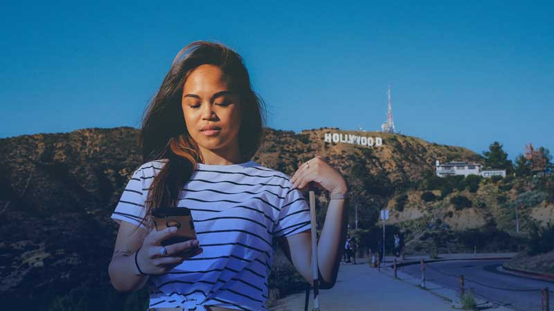 Image of girl looking at her phone and landscape in the background