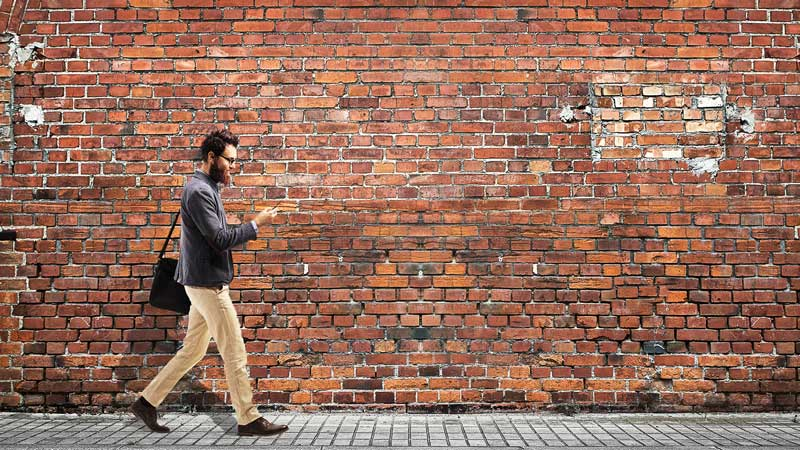 Image of man walking in front of a brick wall