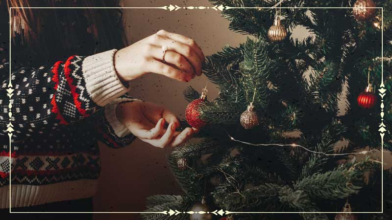 Image of person hanging ornaments on a Christmas tree