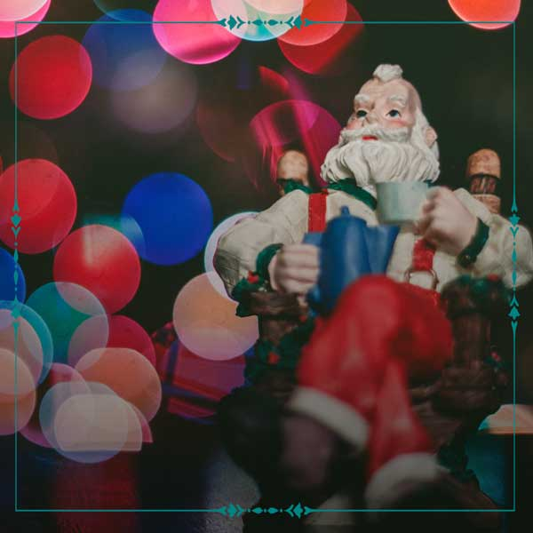 Image of Santa Claus sitting with colorful lights around him