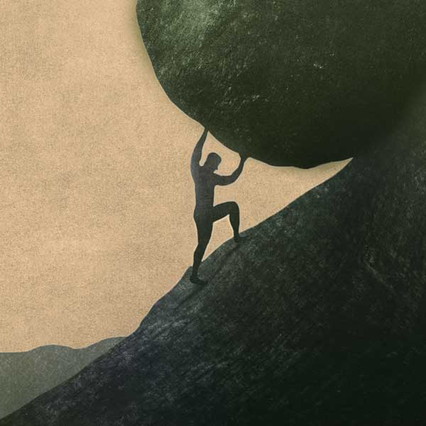 Image of man holding a boulder up a cliff
