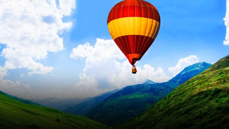 Image of hot air ballon flying over a field