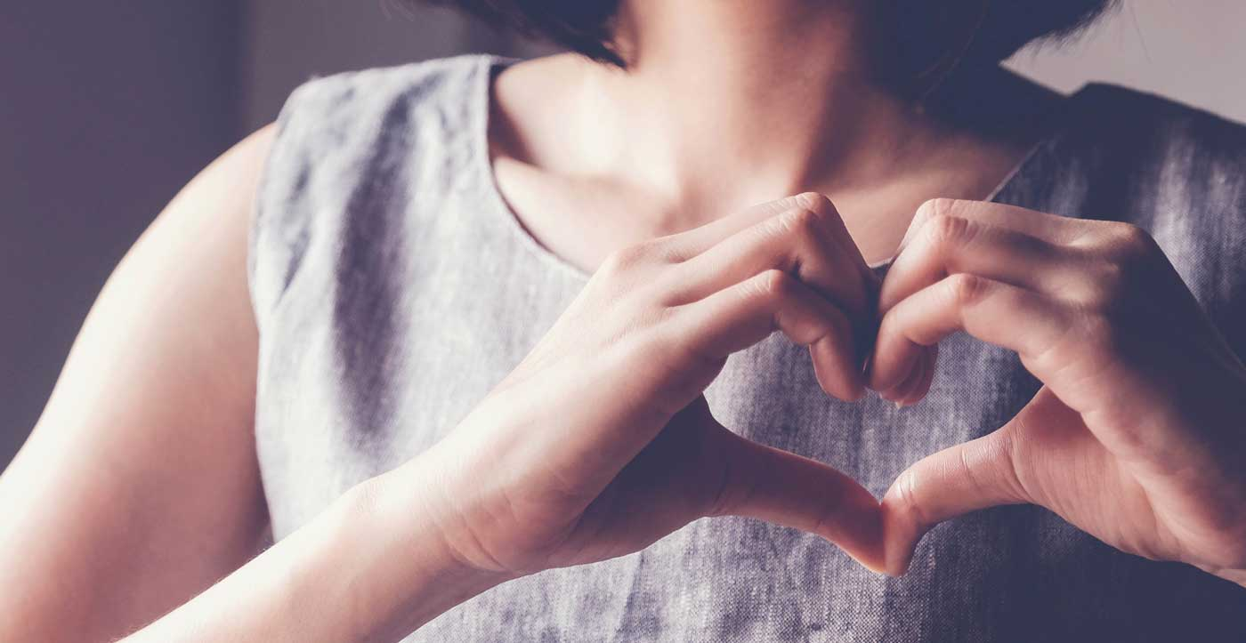 Image of woman holding her hands in the shape of a heart