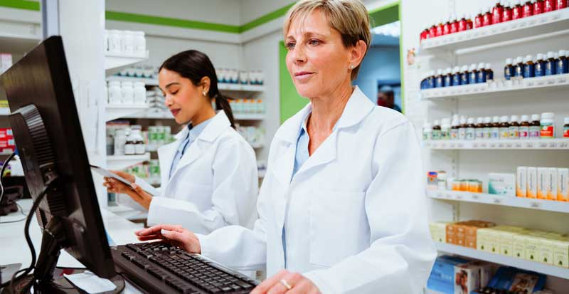 Pharmacist in Pharmacy looking at a computer