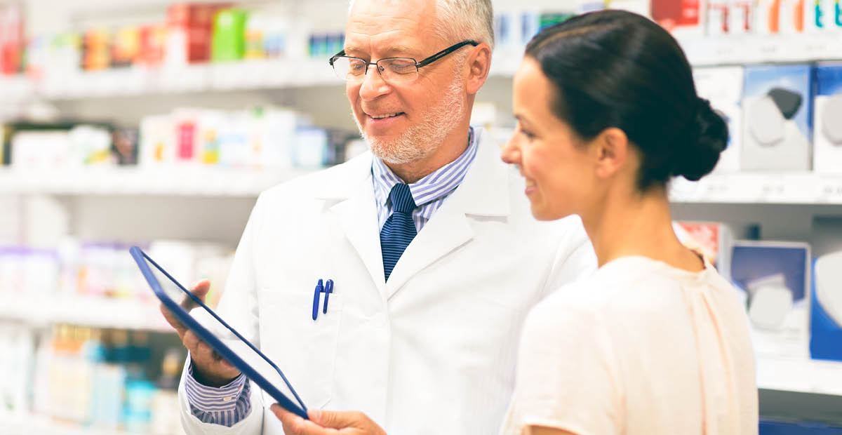 Pharmacist holding clipboard and talking to patient