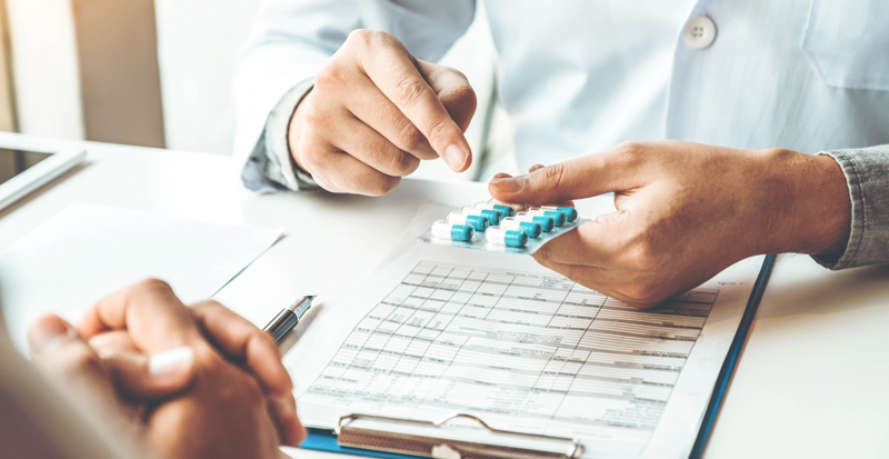 pharmacist pointing to pills and consulting a patient