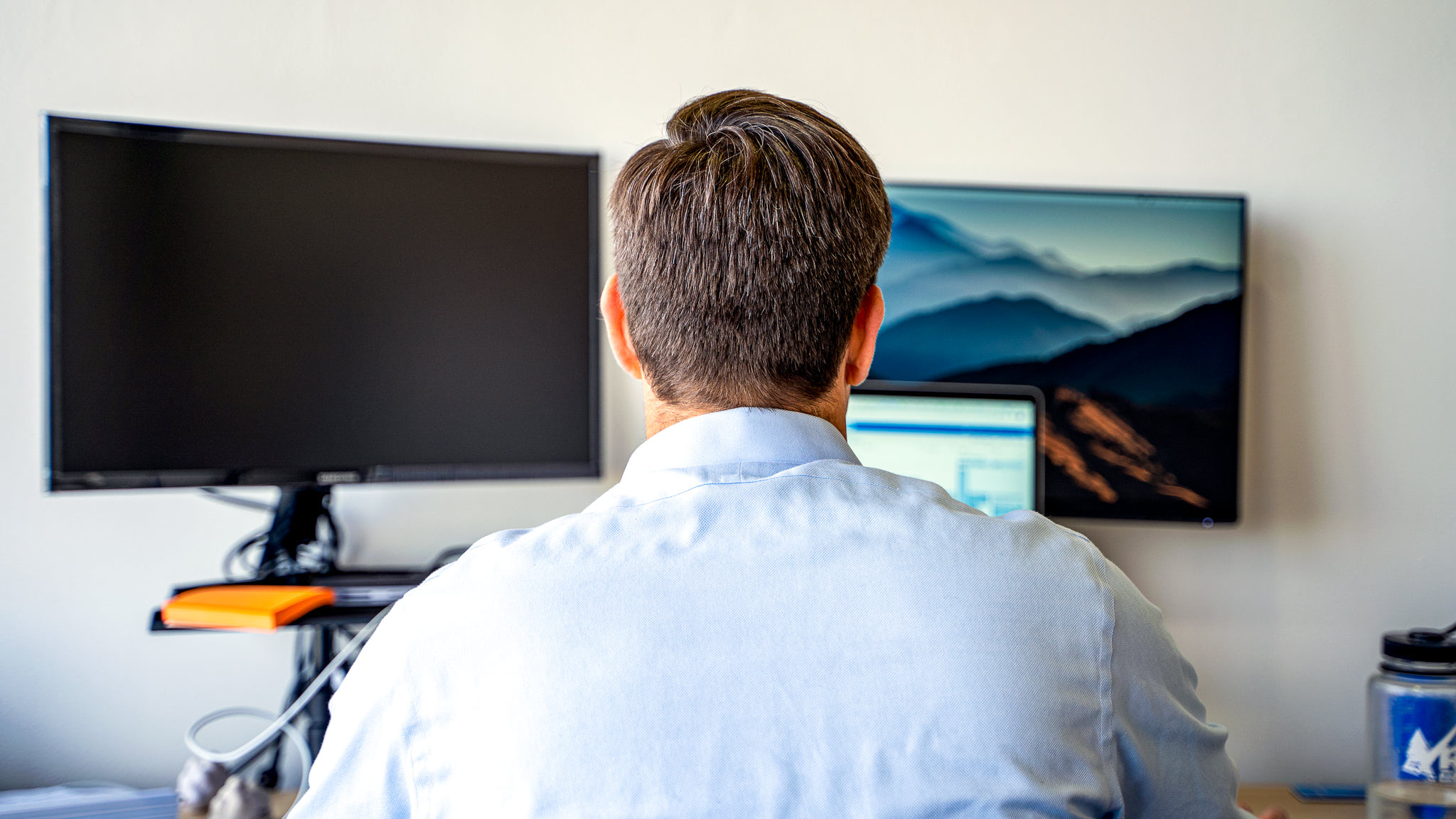 Back of a Dura employee in a blue collared shirt looking at two computer screens that