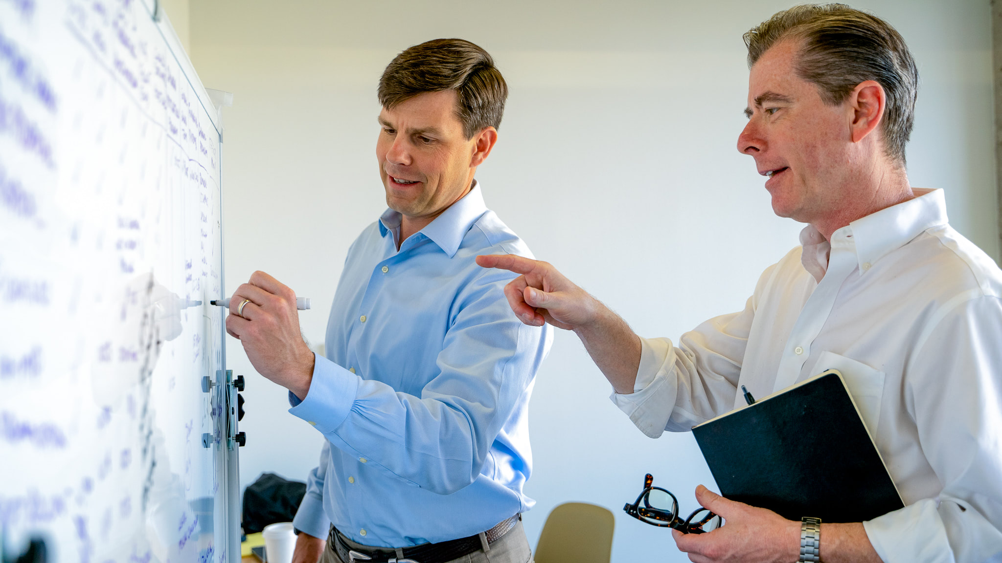 Dura CEOS smiling, meeting and taking notes on a white board