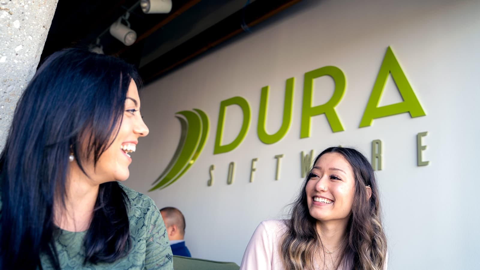 Two dura employees laughing with in front of a dura software wall sign.