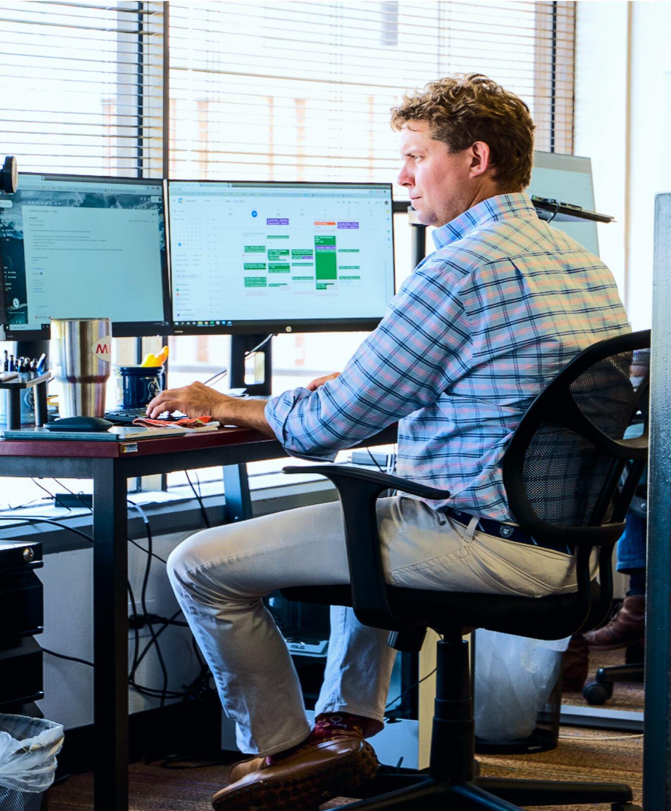 Man sitting at desk looking at dual monitors