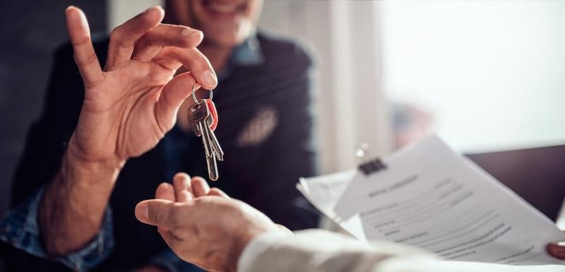 Business deal hands handing over keys with paperwork