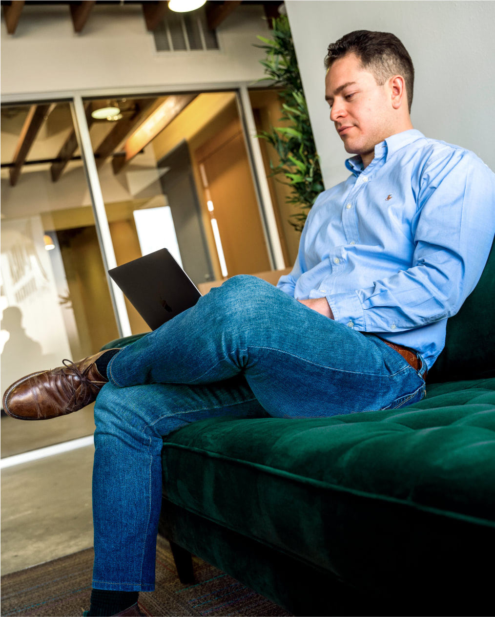 Man in semi-professional clothing sitting on couch working on a laptop