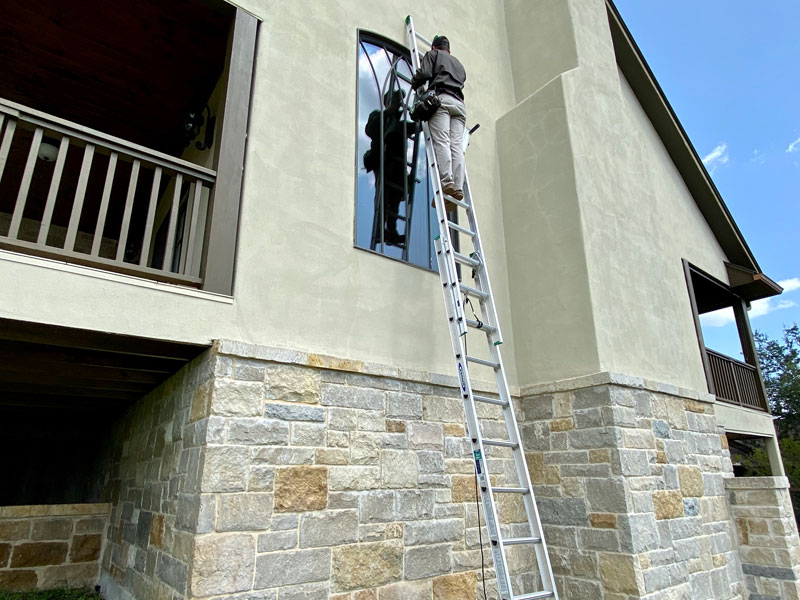 A window cleaner reaching a second-floor window in Kerrville.