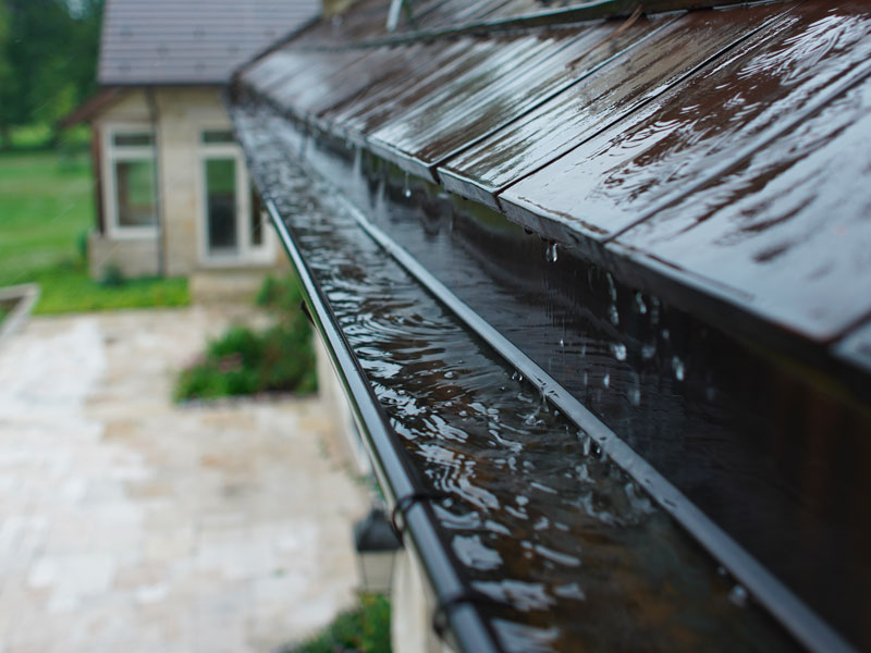 A clean gutter draining water while it rains.