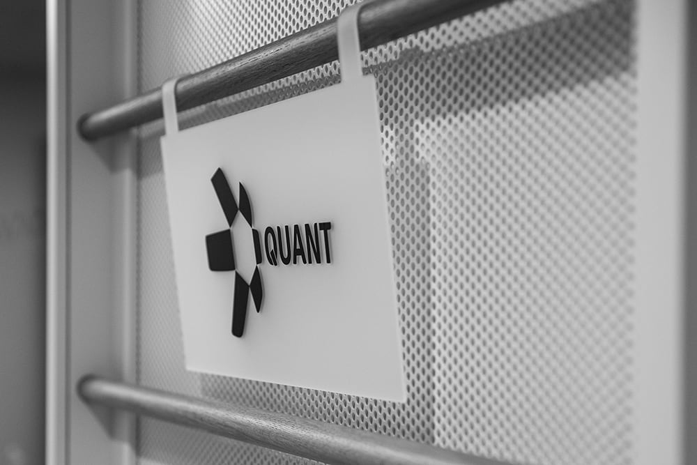 where it all began, Quant sign, black logo on white background