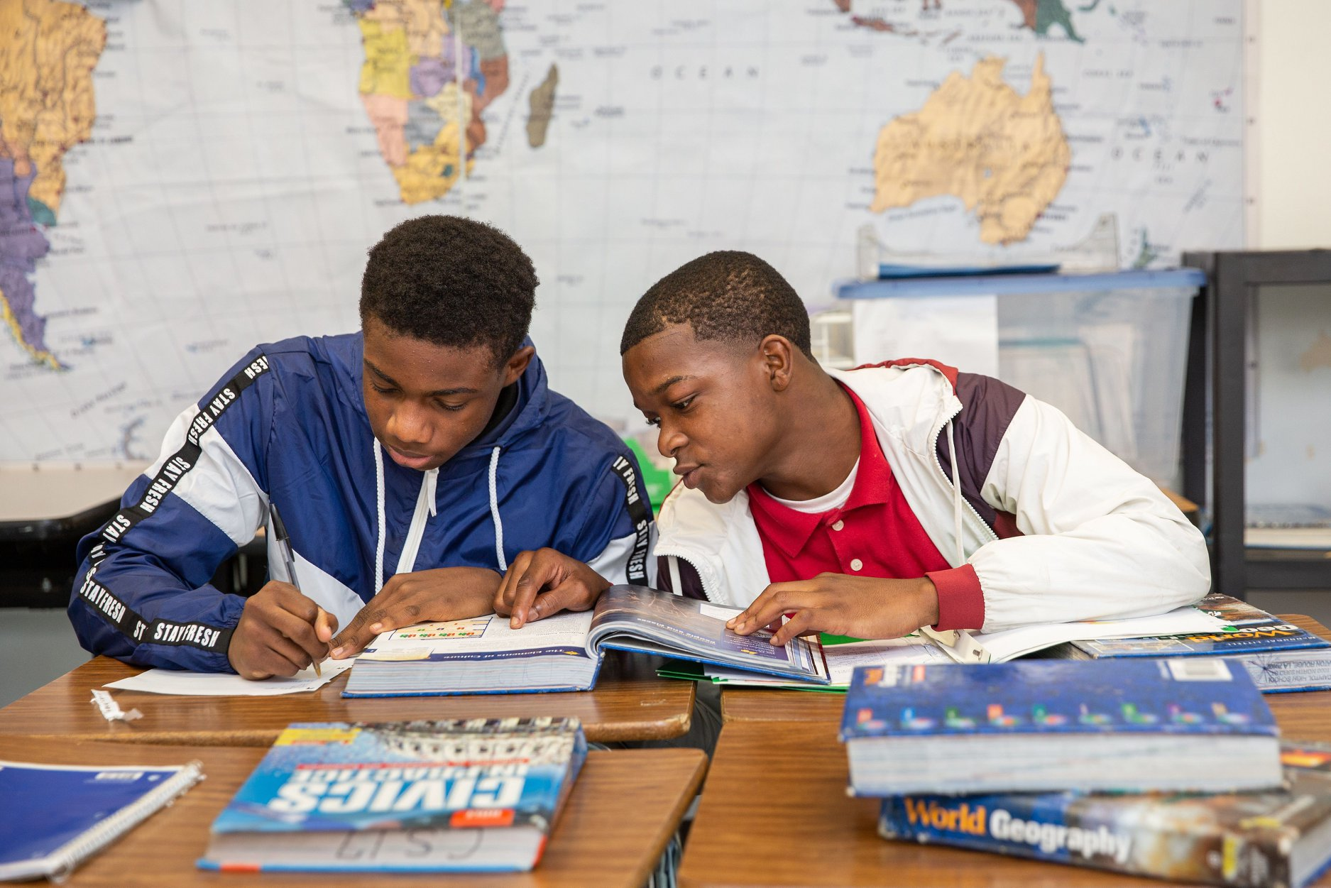 Two high school students reading a text book together.