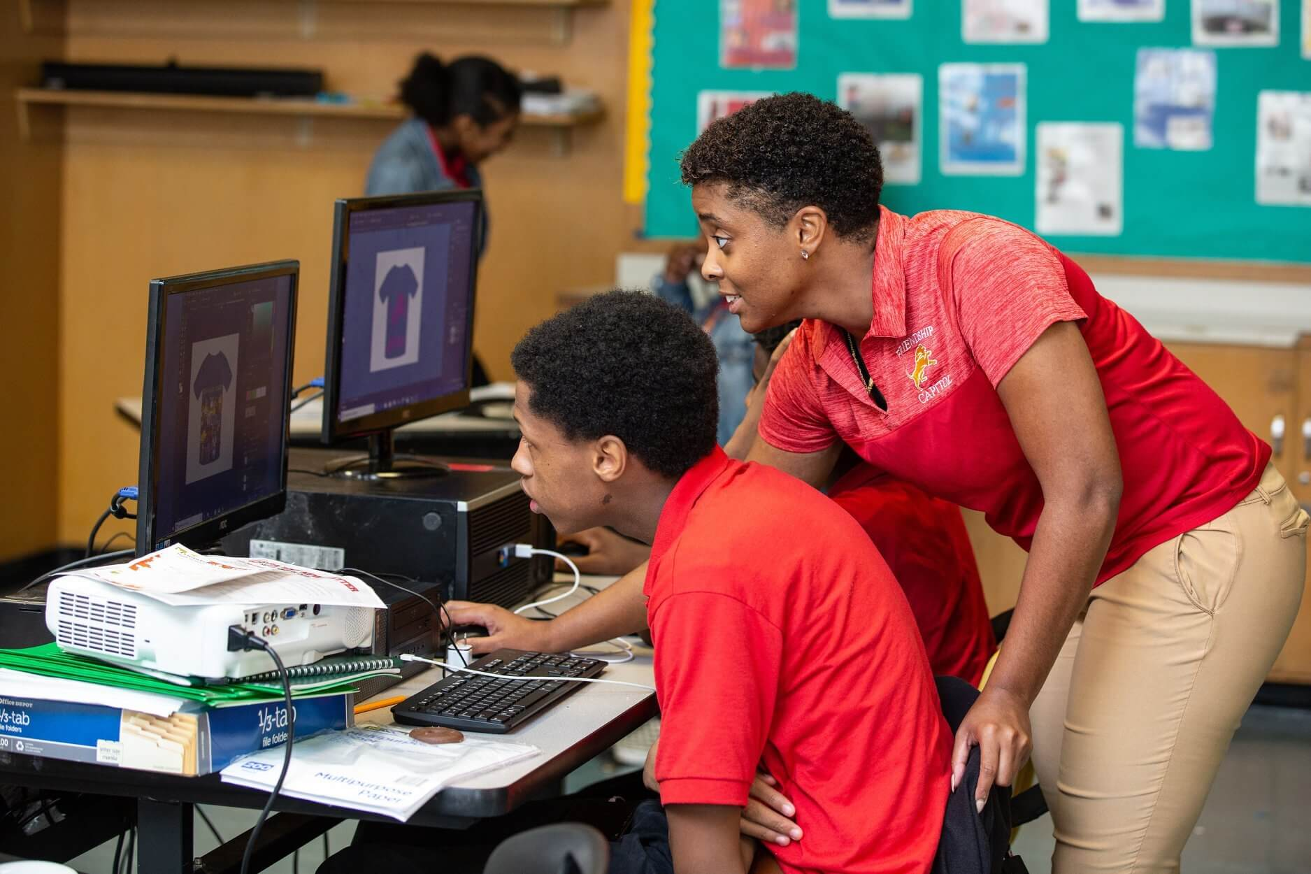A teacher and student look at a computer as they collaborate on a t-shirt design project.