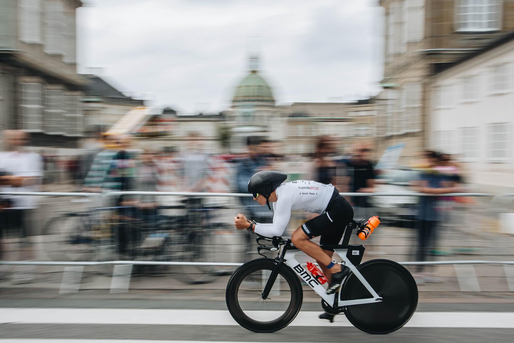 Man racing very fast on a bike past a big crowd in Copenhagen