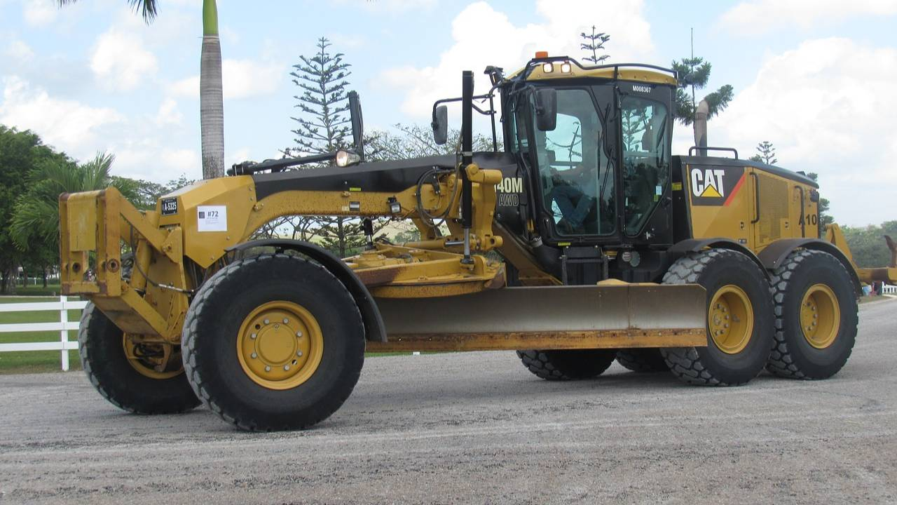 Cat yellow grader side profile on a road