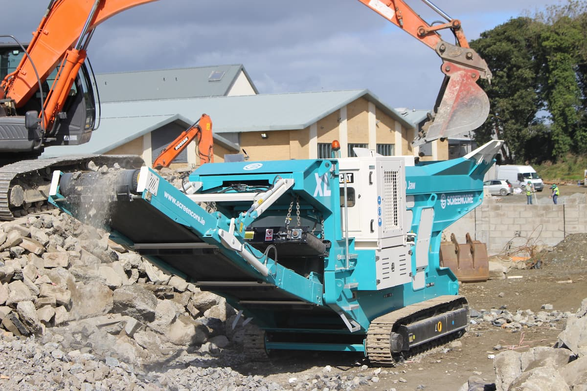 excavator shovelling stone into a green screencore crusher
