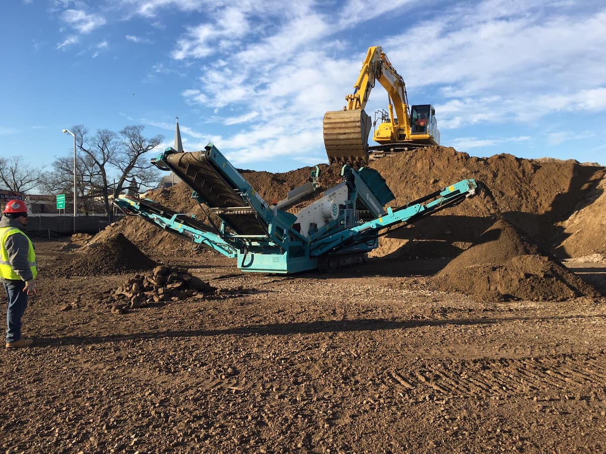 orange excavator and green screener processing soil