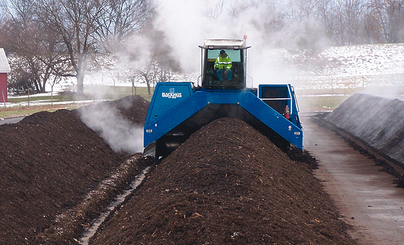 machine turning a row of compost