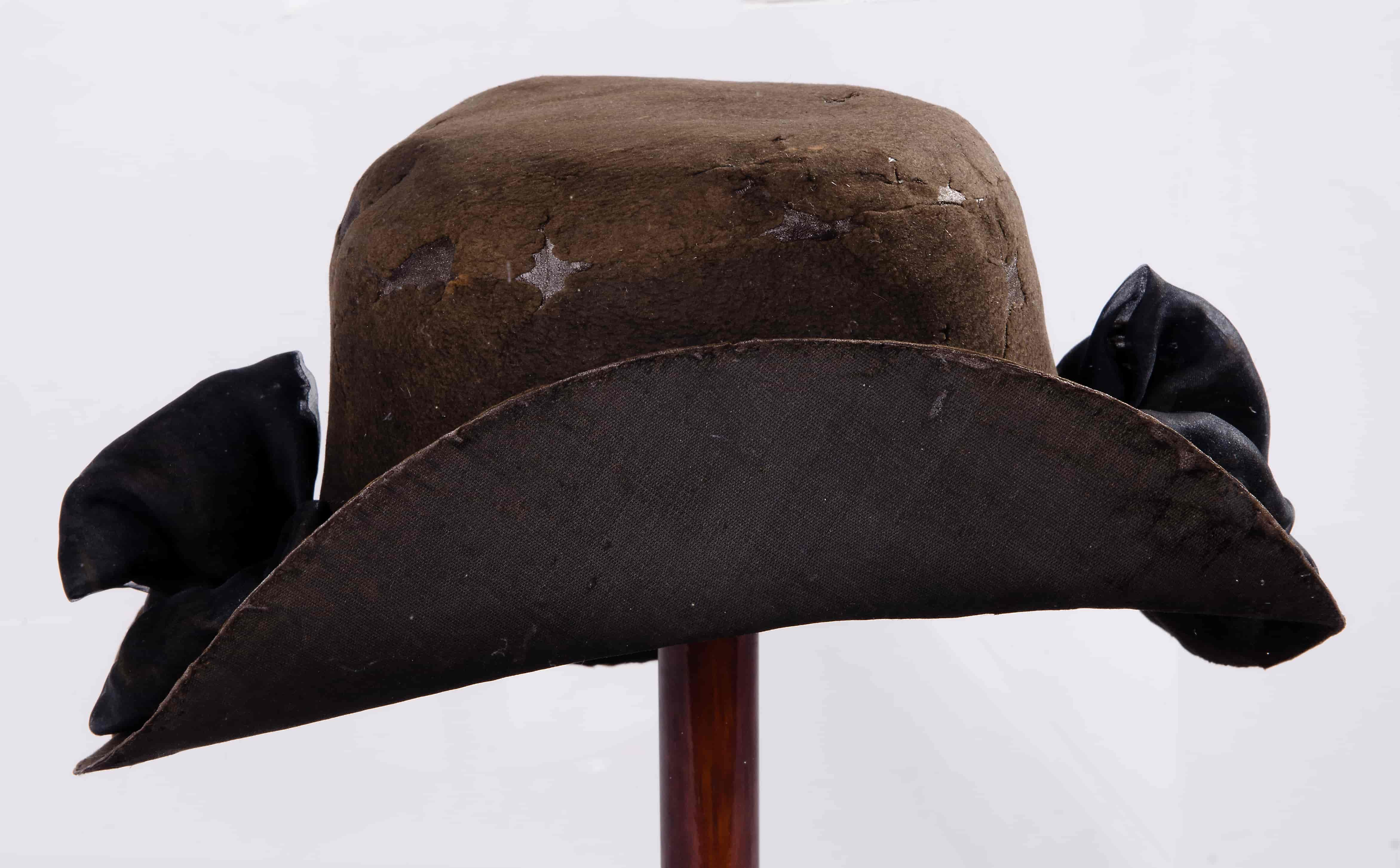 Photo of a brown hat with black bows and upturned brim to front. The hat looks well worn with some bare patches and is displayed on a stand. White background.