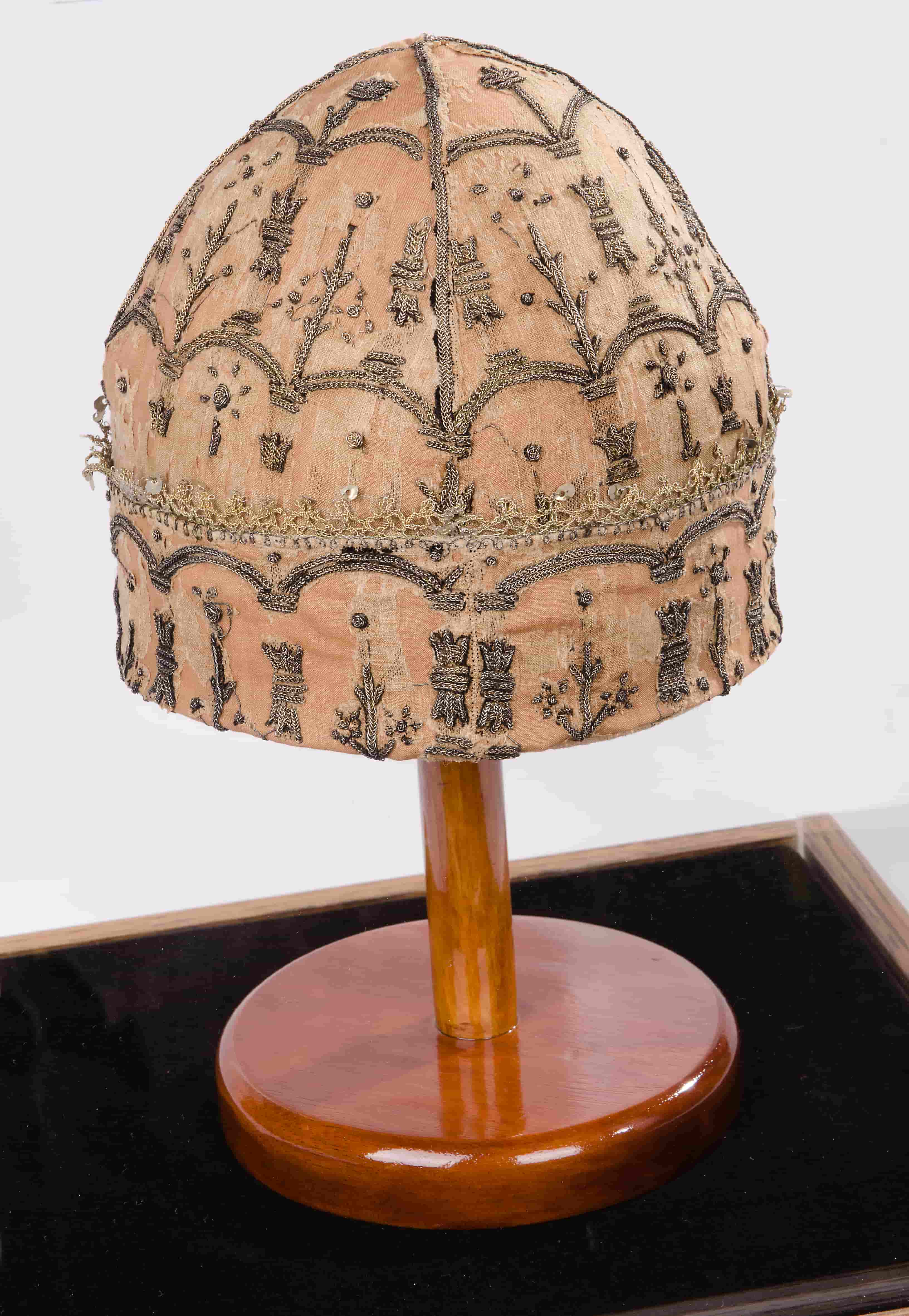 Photo of round faded red hat with ornate embroidery on a polished wooden stand on a black fabric cloth with a white background.