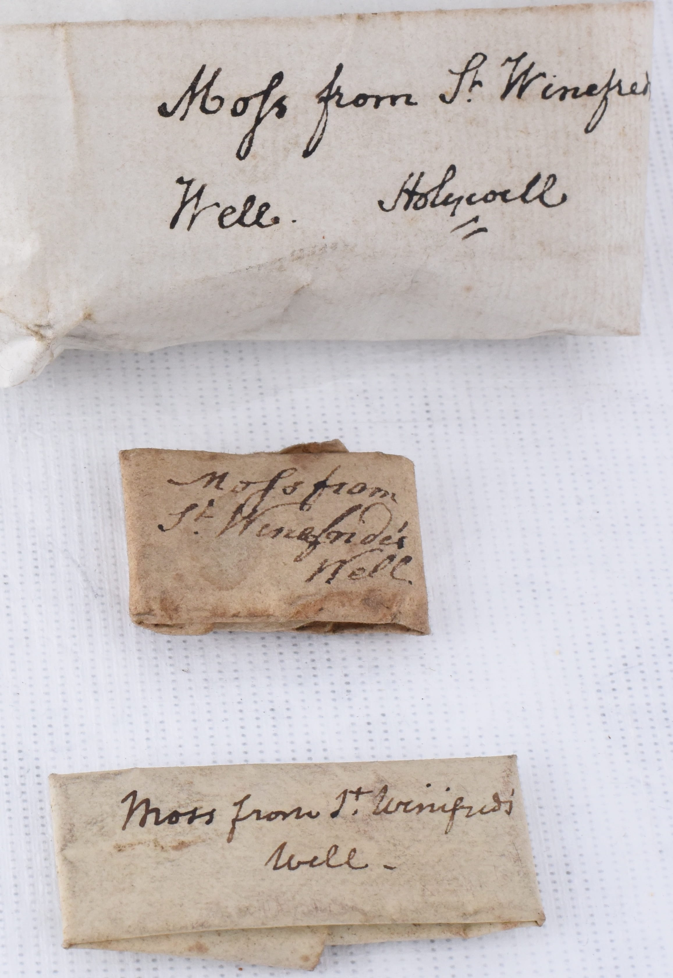 Photo of three varying sized and shades of white to brown paper parcels all handwritten with inscription: Moss from St Winefride's Well. On a white background.