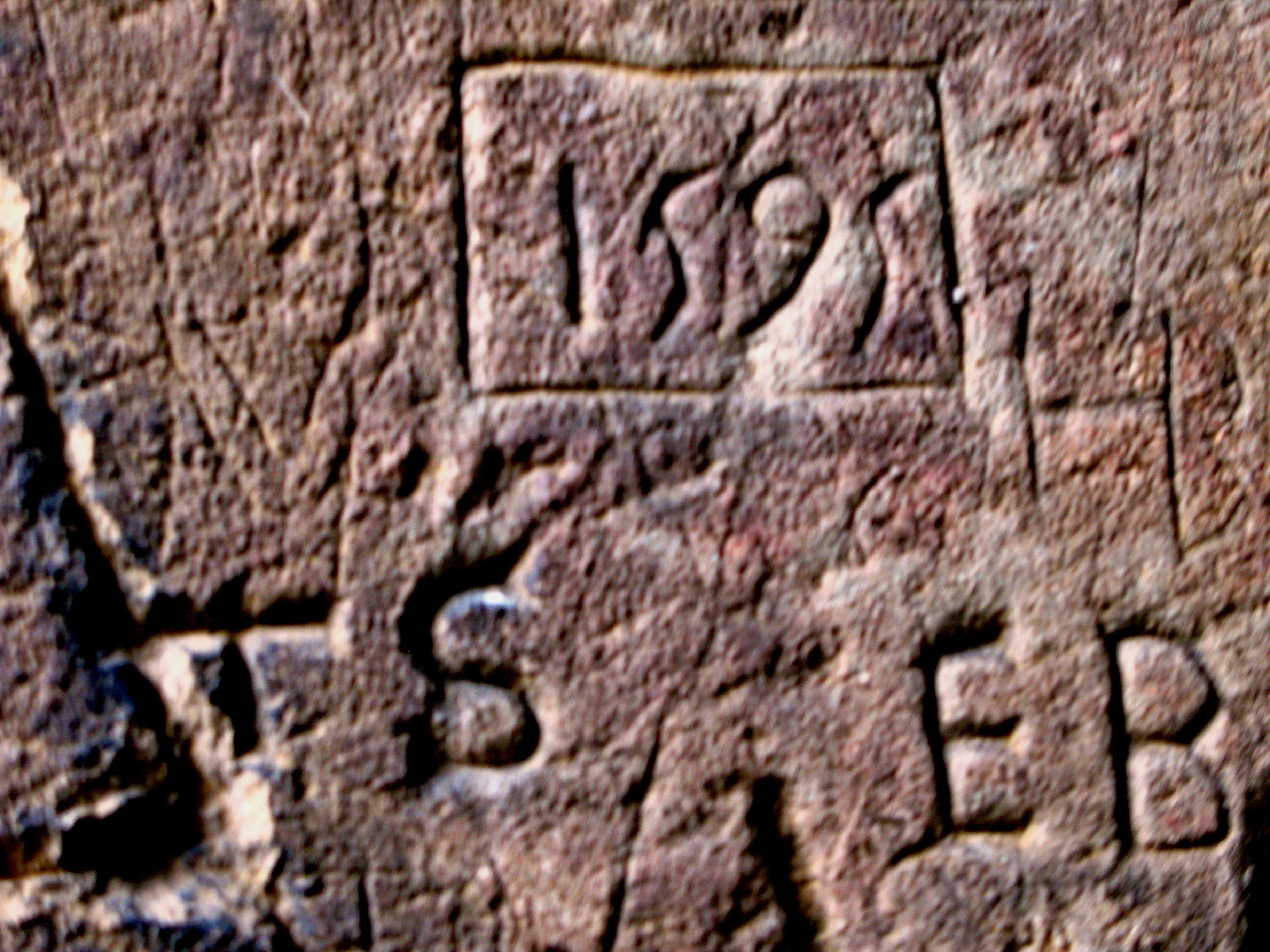 The date fifteen ninety five carved into stone surrounded by carvings of other letters and numbers